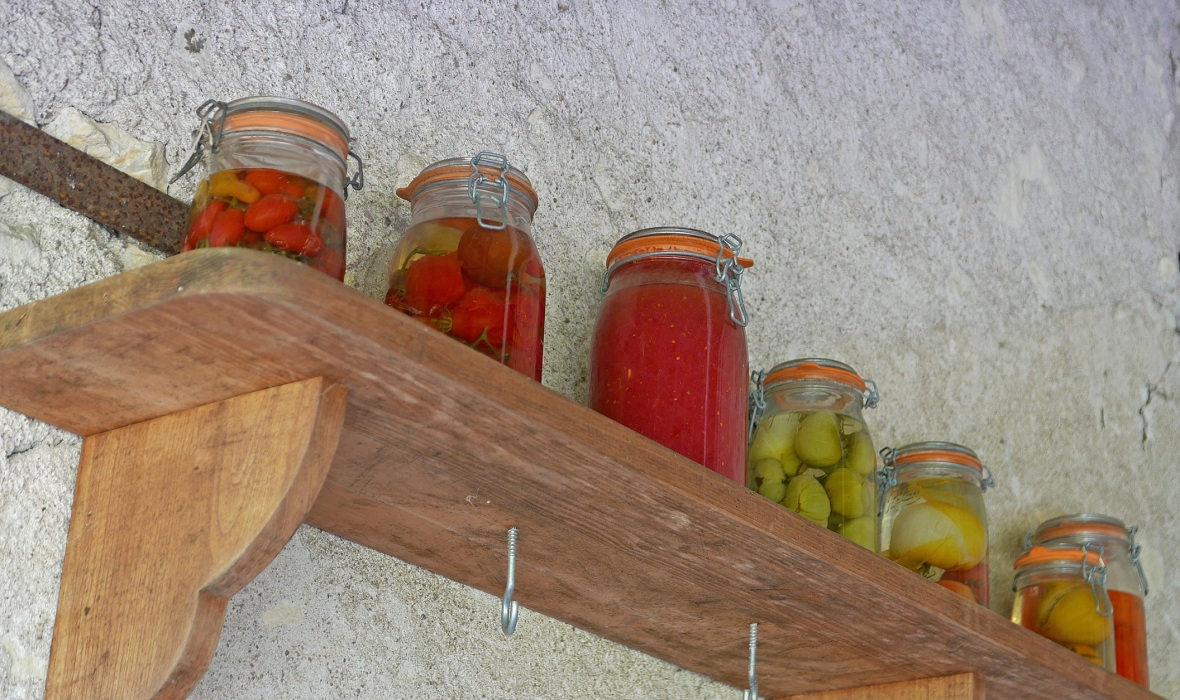 Preserved tomatoes on a wooden shelf